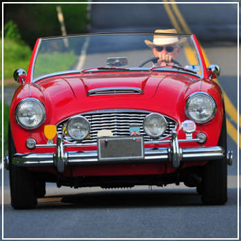 older man driving a red vintage car