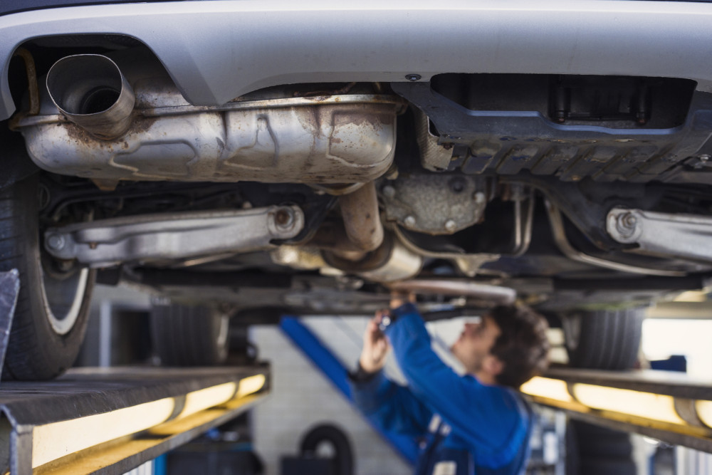 Mechanic working on vehicle exhaust system