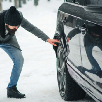 man checking tire in snow