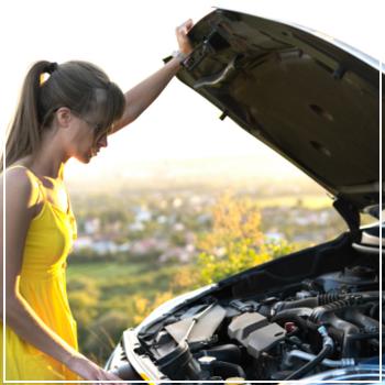 woman looking under car hood